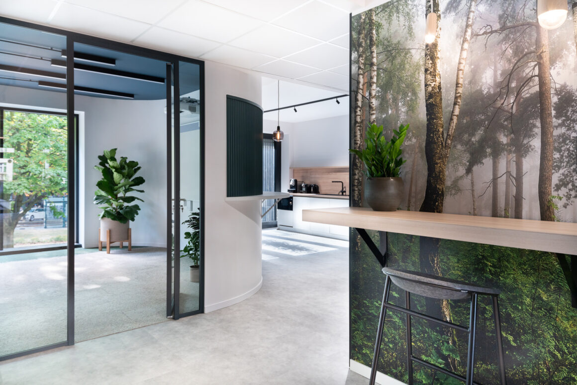 BECI Brussels workspace design and renovation by Space Refinery - curved wall high wall tables forest wallpaper
